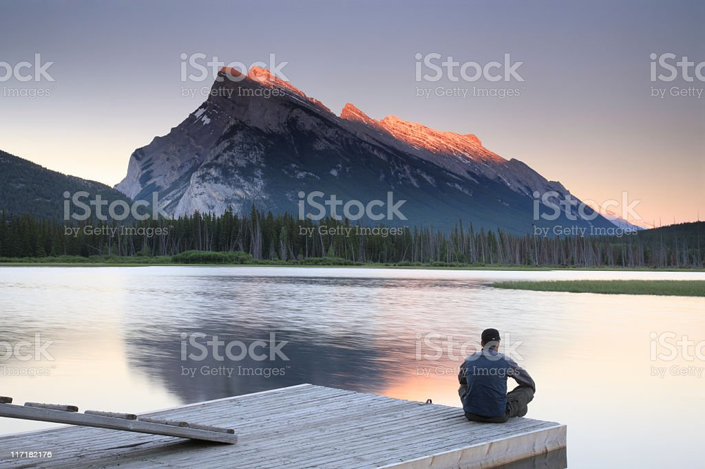 Man sitting on edge of dock by Mount Rundle, Banff royalty-free stock photo