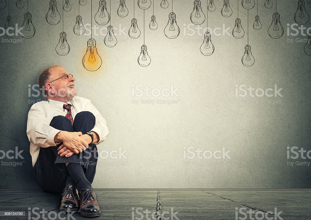 Man sitting on floor looking up at light idea bulb stock photo