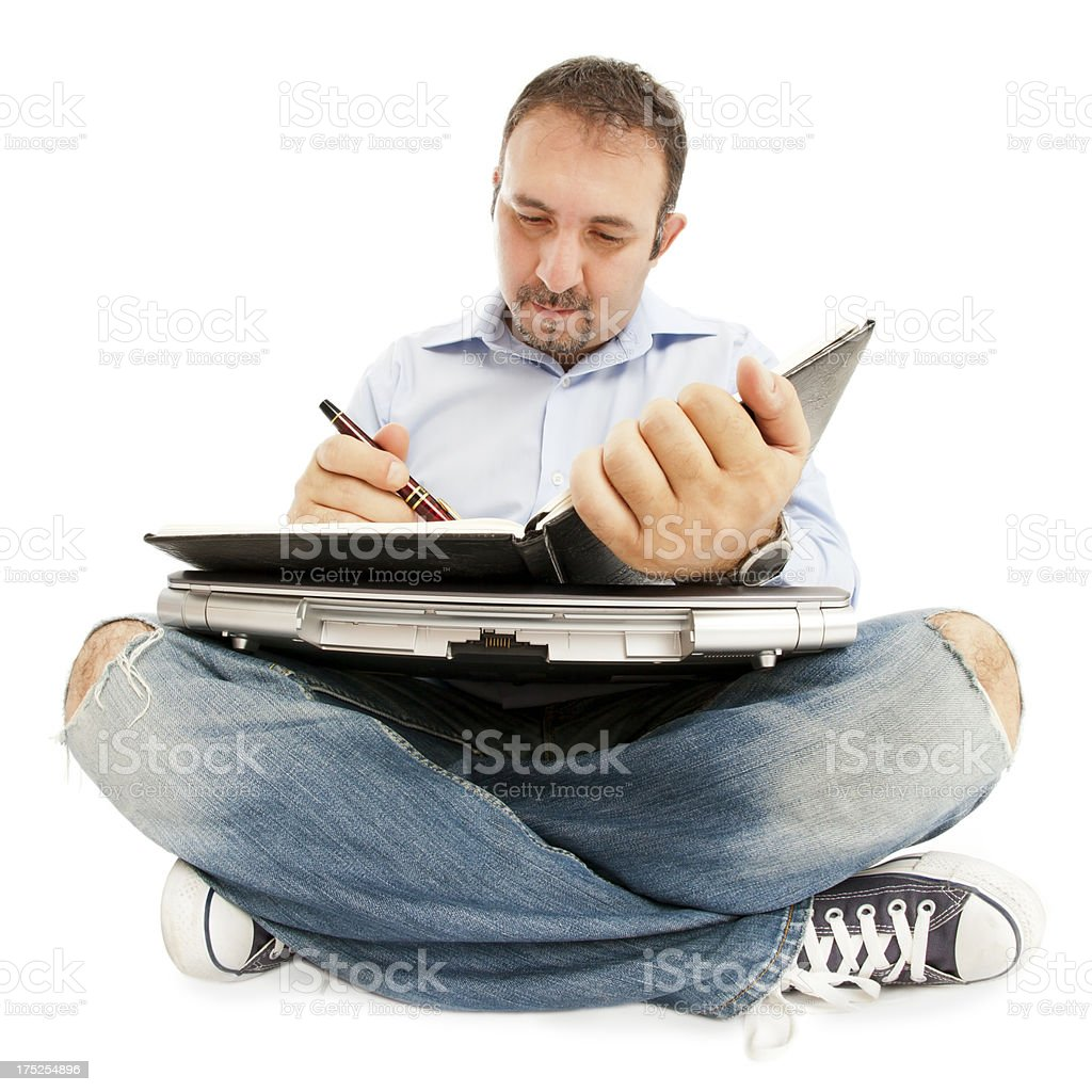 Man Sitting on floor with laptop, agenda etc. royalty-free stock photo