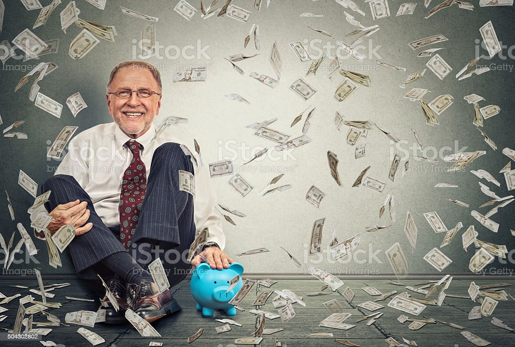 Man sitting on floor with piggy bank under money rain stock photo