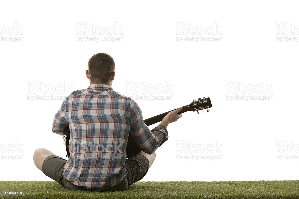 Man sitting on grass and playing a guitar royalty-free stock photo
