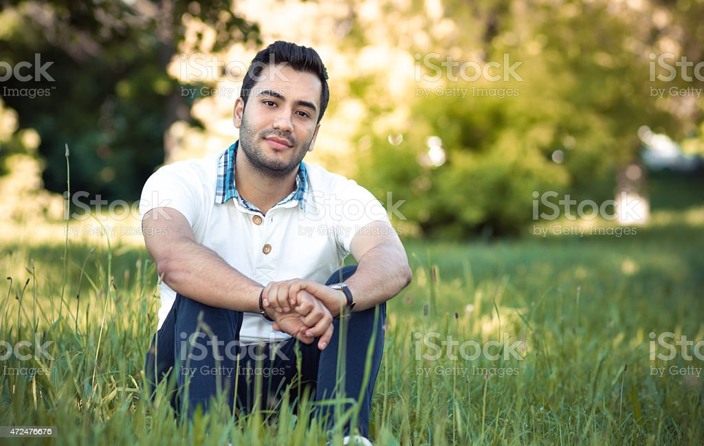 Man sitting on grass in forest stock photo