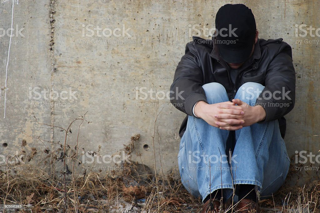 Man sitting on ground folding hands royalty-free stock photo