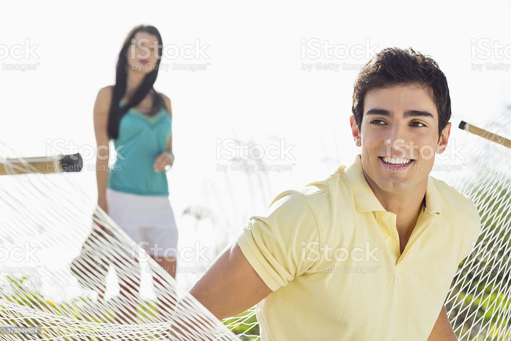 Man Sitting On Hammock With Woman In Background. royalty-free stock photo