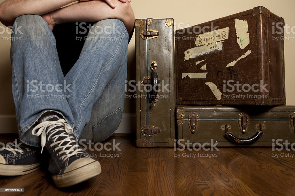 Man sitting on hardwood floor by packed bags ready to leave  royalty-free stock photo