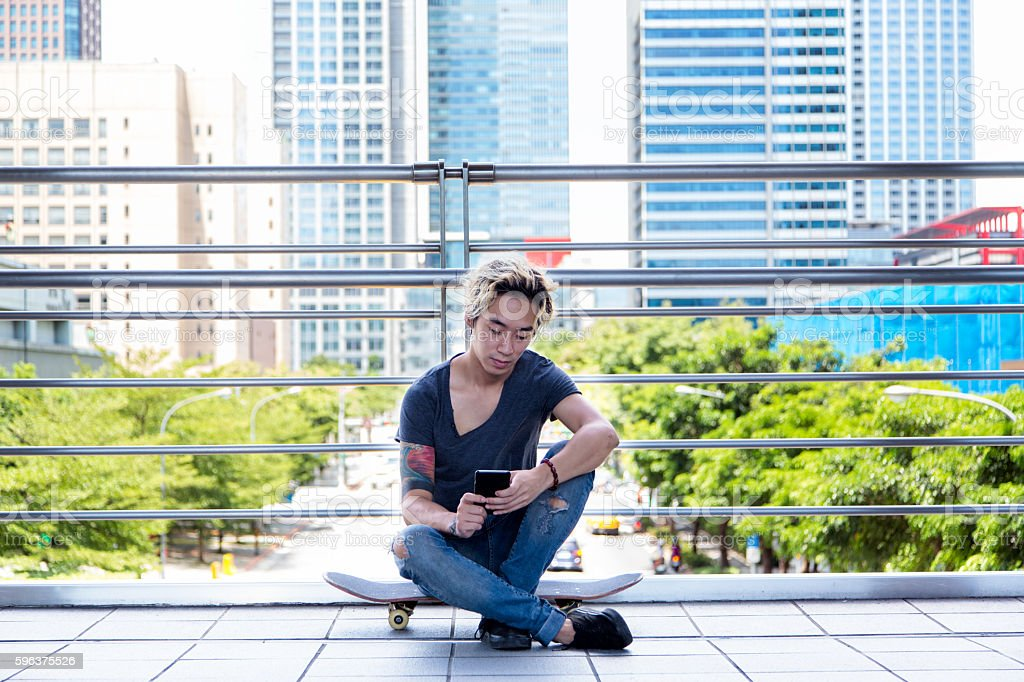 Man sitting on his skateboard and looking at his phone stock photo