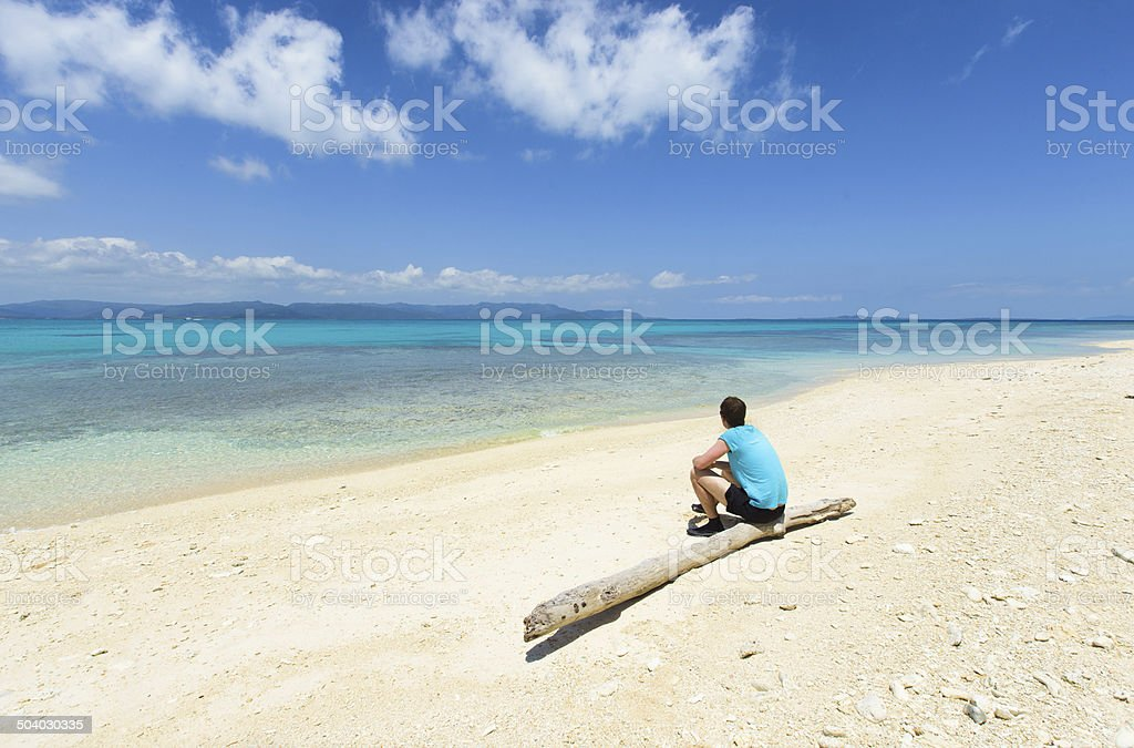 Mann sitzt auf einer idyllischen tropischen Strand Paradies in Okinawa, Japan Lizenzfreies stock-foto