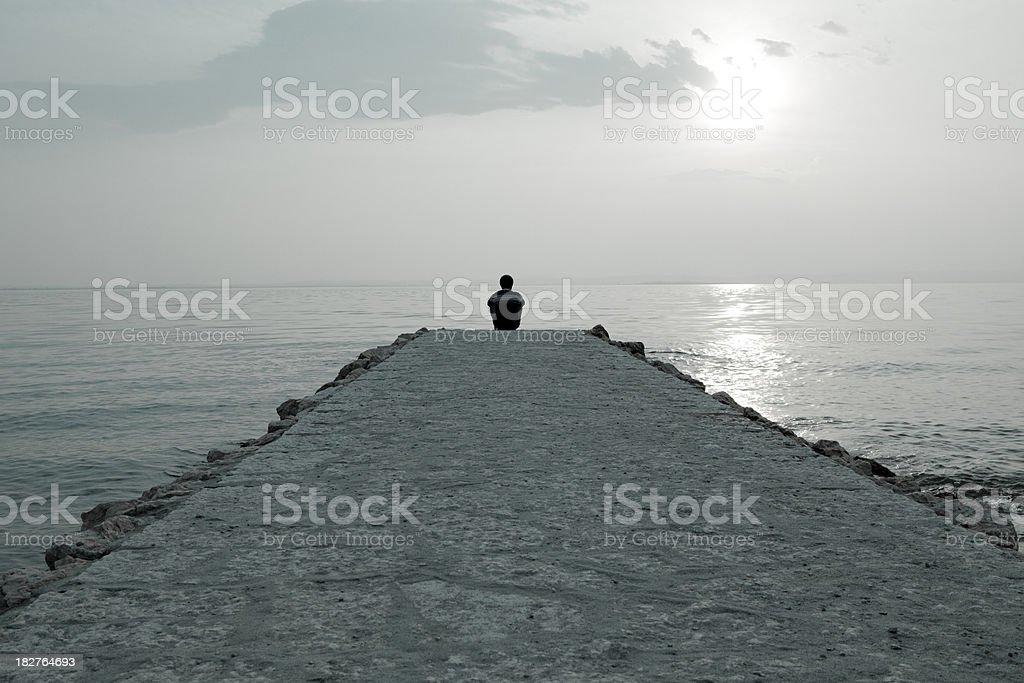 Man sitting on jetty stock photo