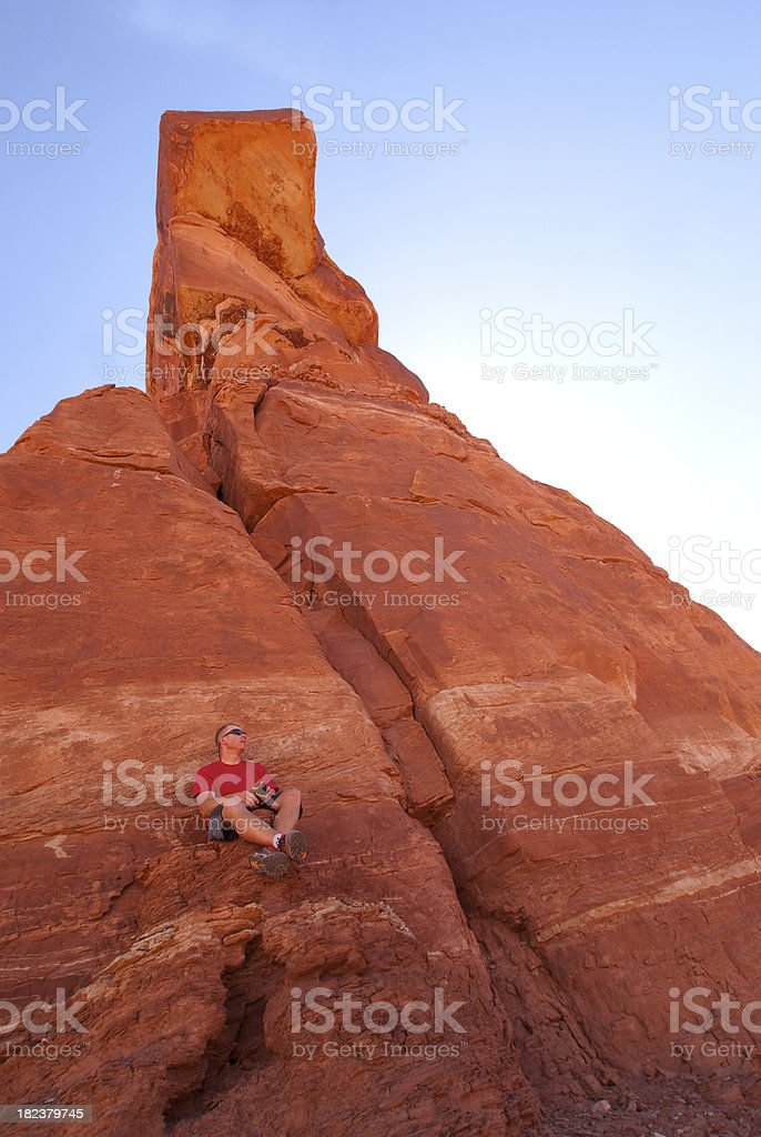 man sitting on landscape sandstone rock formation royalty-free stock photo
