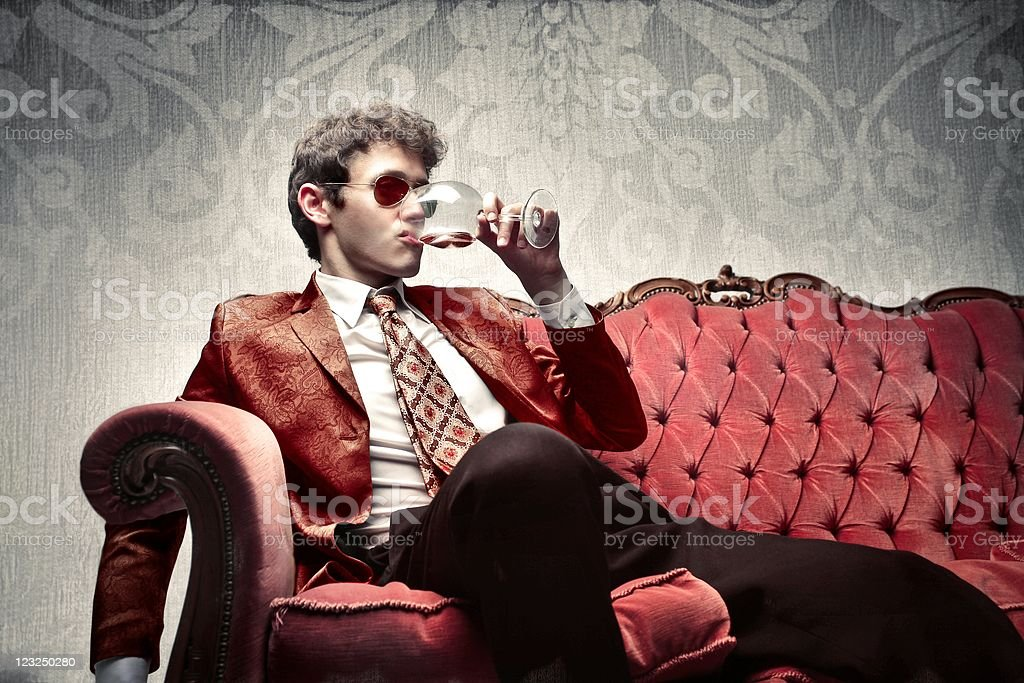 Man sitting on luxurious couch drinking wine stock photo