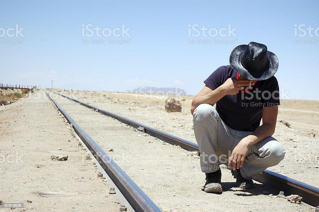Man sitting on railway and smoking royalty-free stock photo
