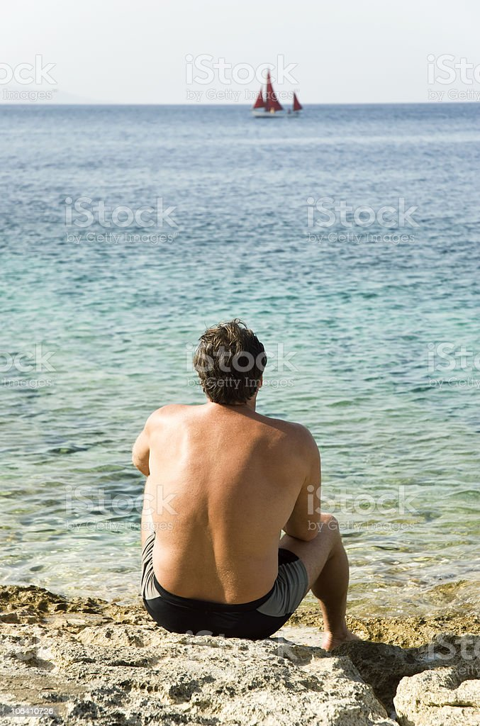 man sitting on rocks by the sea royalty-free stock photo