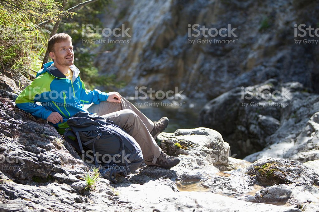 Man sitting on rocks near stream stock photo