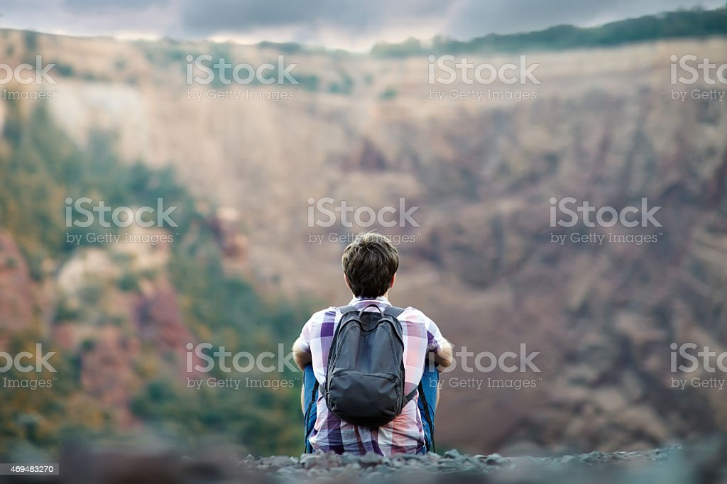 Man sitting on rocky cliff stock photo