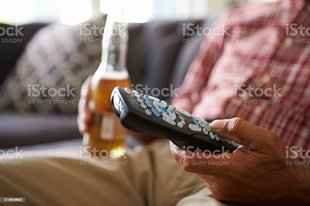 Man Sitting On Sofa Holding TV Remote And Bottle Of stock photo