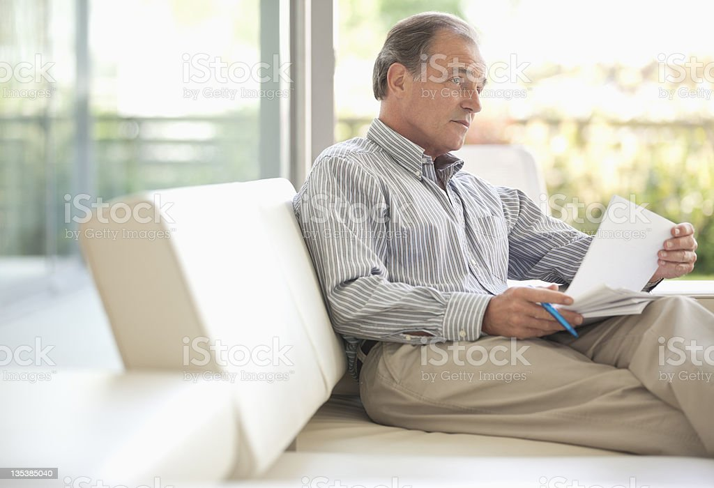Man sitting on sofa looking at paperwork royalty-free stock photo