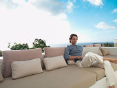 Man sitting on sofa outdoors with laptop and sky
