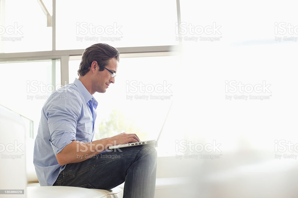 Man sitting on sofa using laptop stock photo