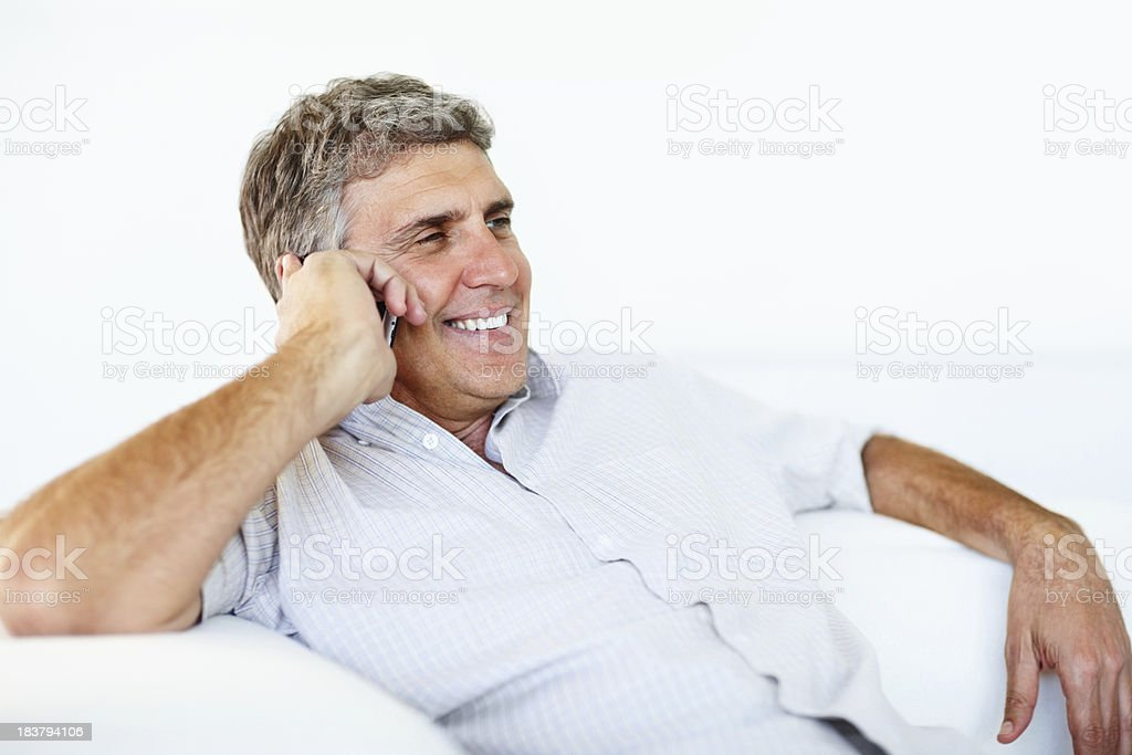 Man sitting on sofa while using his cellphone royalty-free stock photo