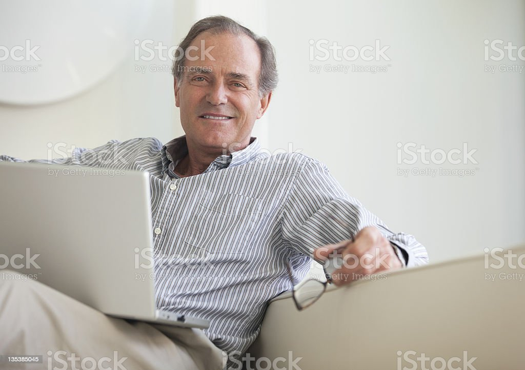 Man sitting on sofa with laptop royalty-free stock photo