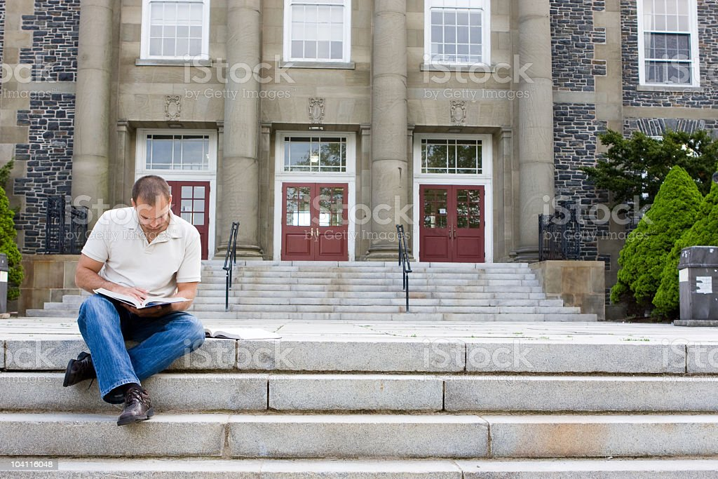Man sitting on stairs reading a book royalty-free stock photo