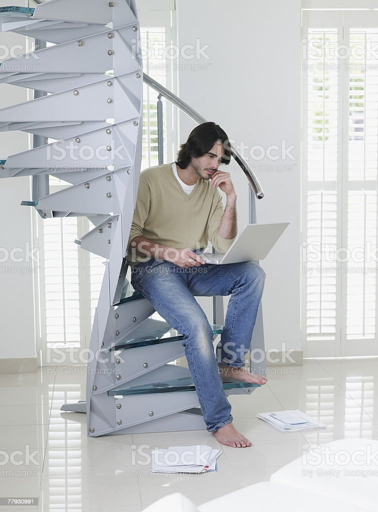 Man sitting on stairs with laptop and paperwork royalty-free stock photo