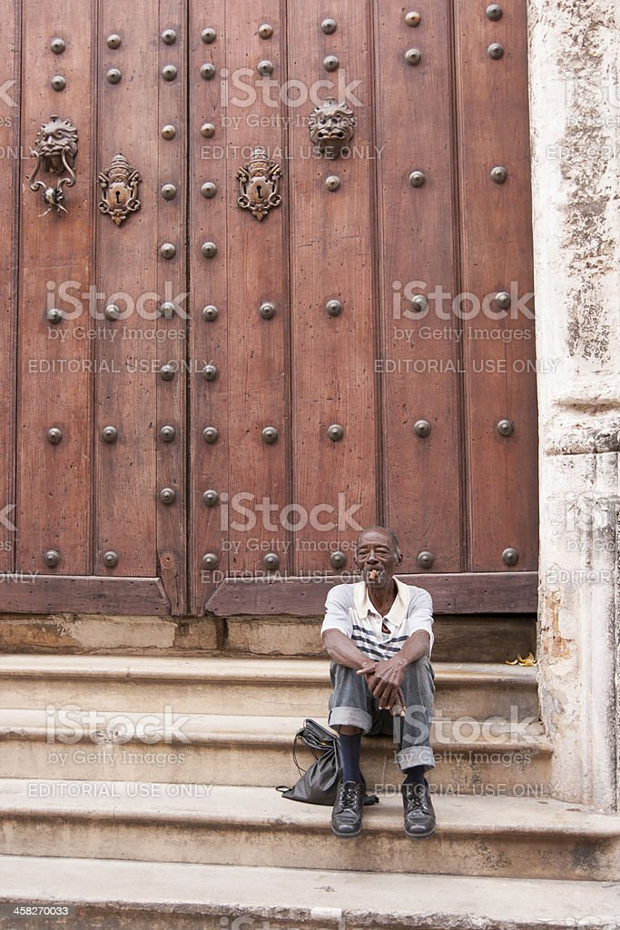 Man Sitting on Steps in Front of Doors, Smoking Cigar royalty-free stock photo