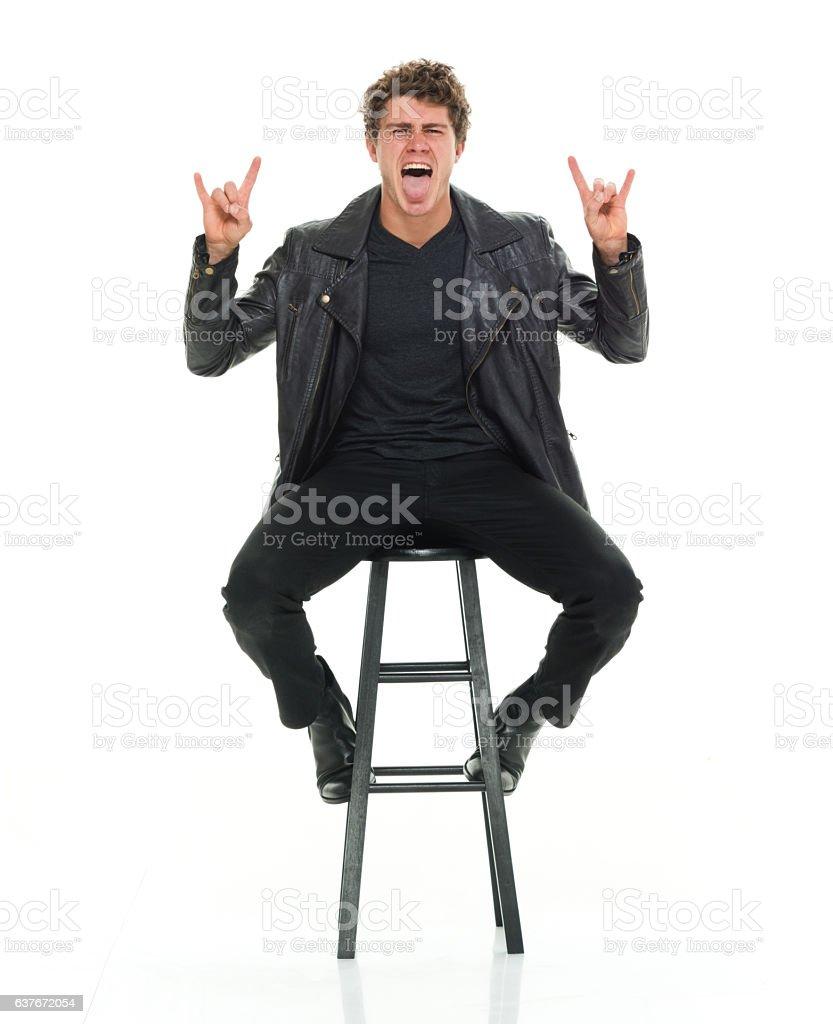Man sitting on stool and giving shaka sign stock photo