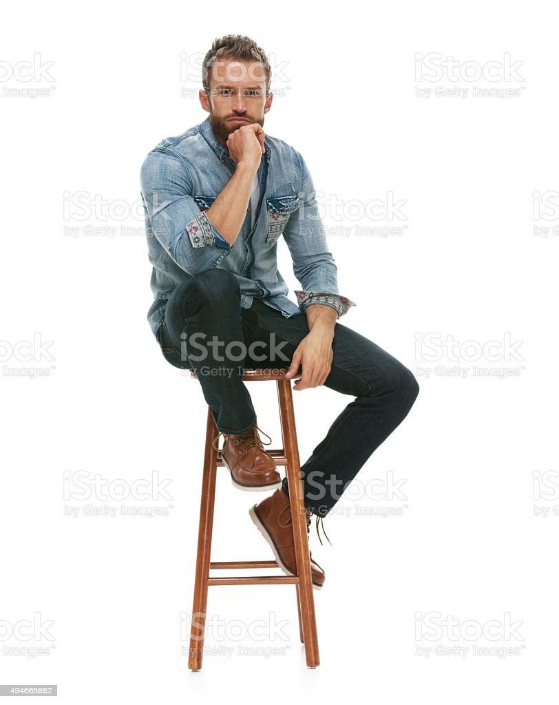 Man sitting on stool and looking at camera stock photo