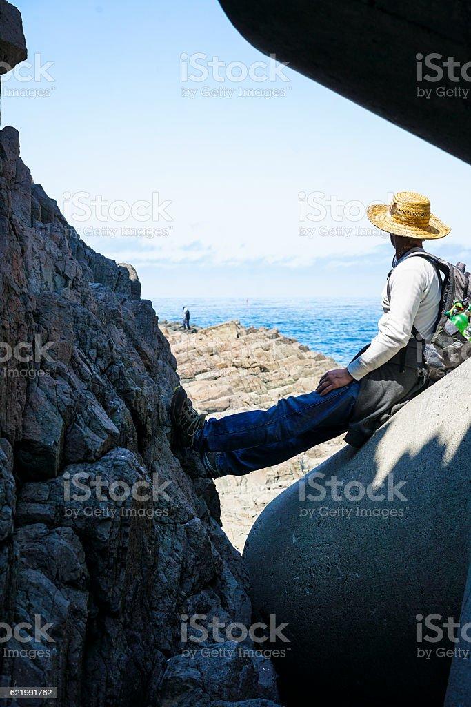 Man sitting on tetrapod  in Utoro, Hokkaido Japan stock photo