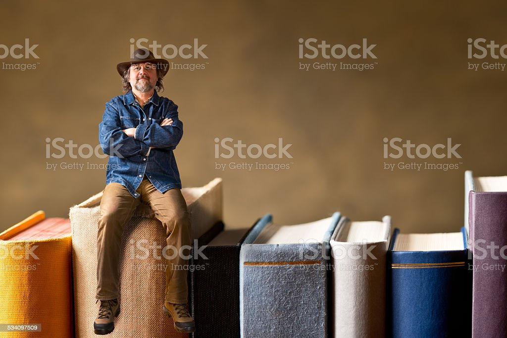 man sitting on the books stock photo