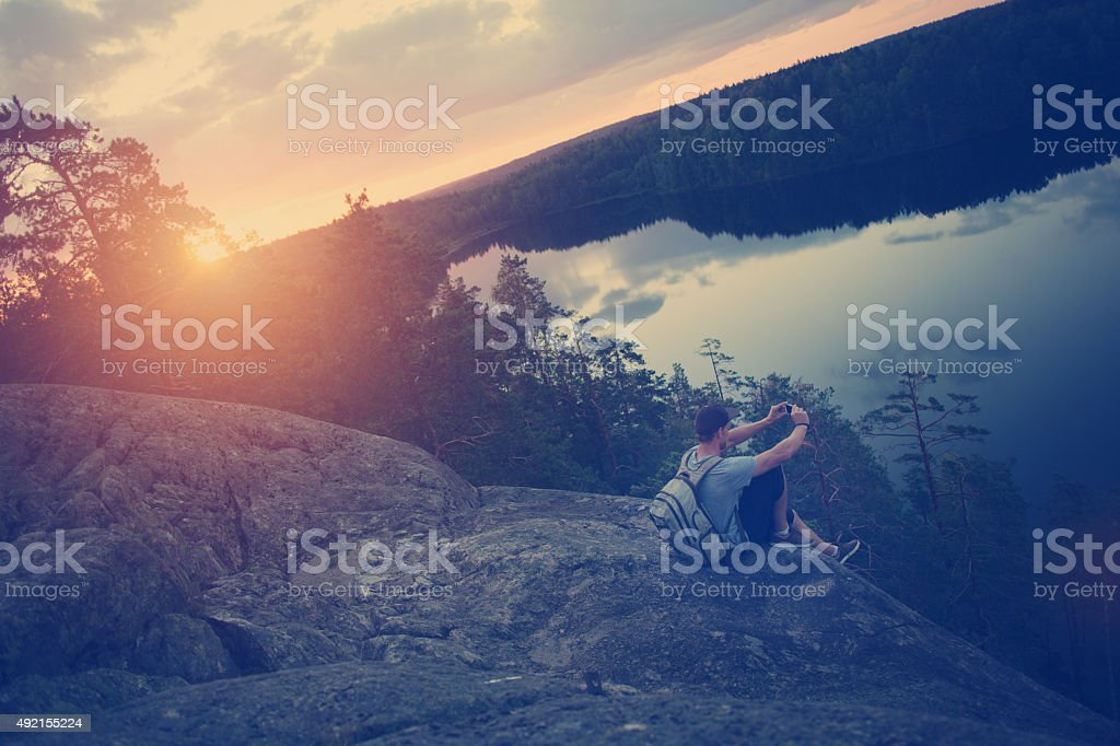 Man sitting on the cliff edge and taking photo stock photo