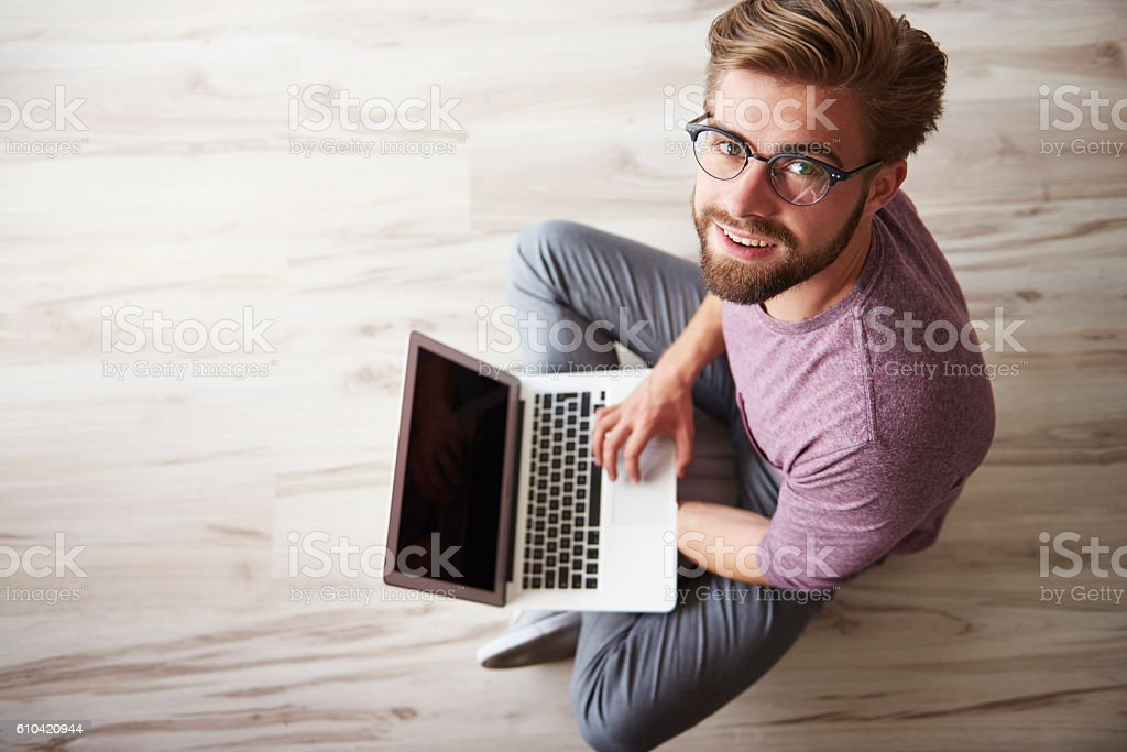 Man sitting on the floor and using the laptop stock photo