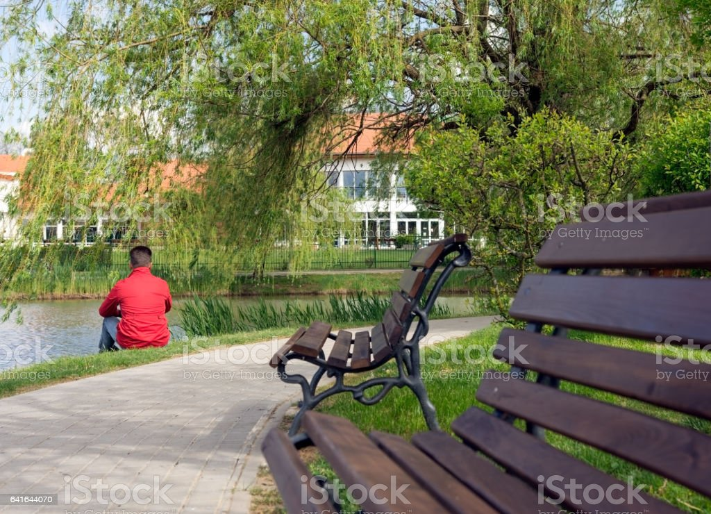 Man sitting on the grass by the lake near the park with benches stock photo