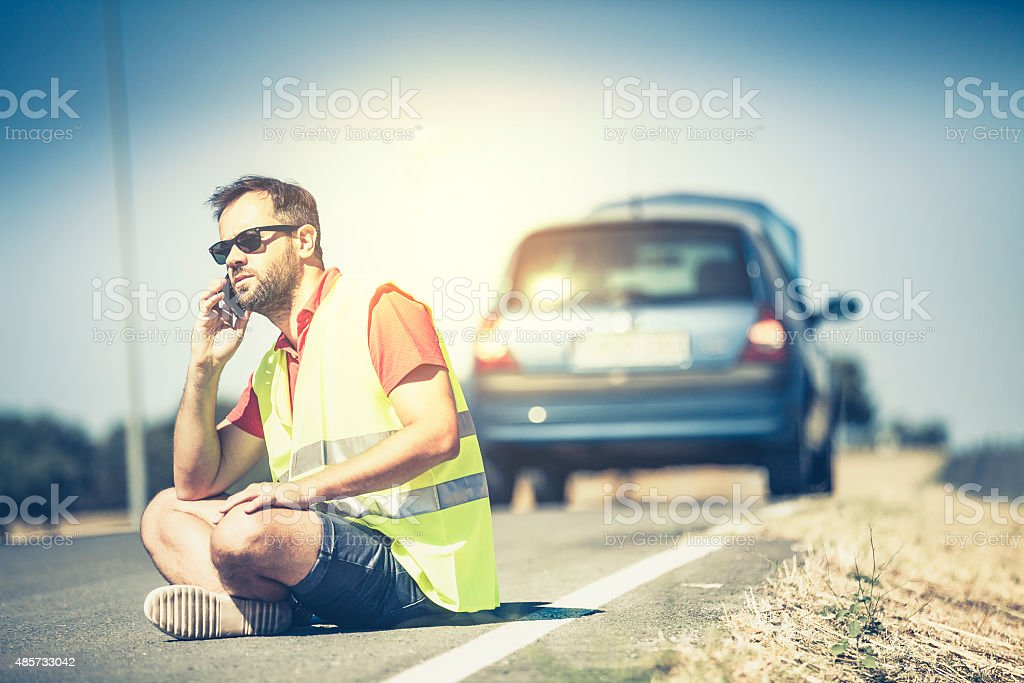 Man sitting on the road after car breakdown. stock photo