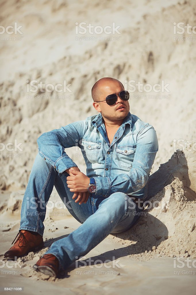 man sitting on the sand in glasses royalty-free stock photo
