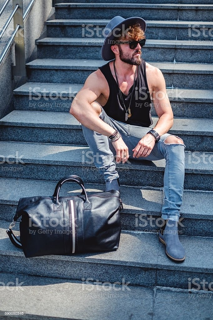 Man sitting on the staris with bag beside stock photo