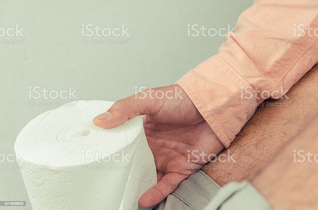 man sitting on the toilet with toilet paper stock photo