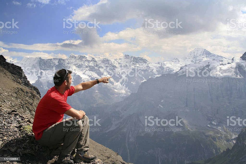 Man Sitting on Top of Mountain and Pointing a Direction stock photo