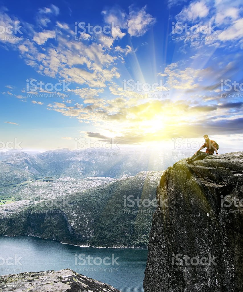 man sitting on top of Norway mountain. Conceptual design stock photo