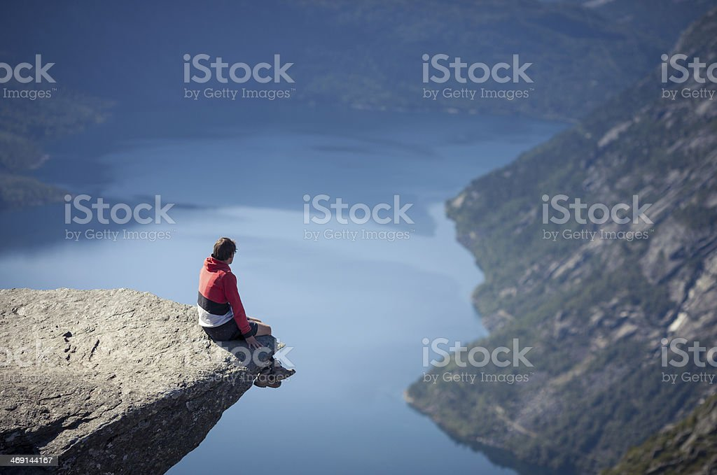 man sitting on trolltunga rock in norway stock photo