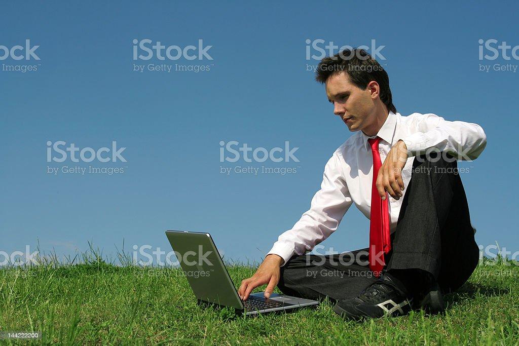 Man sitting outdoors using laptop royalty-free stock photo