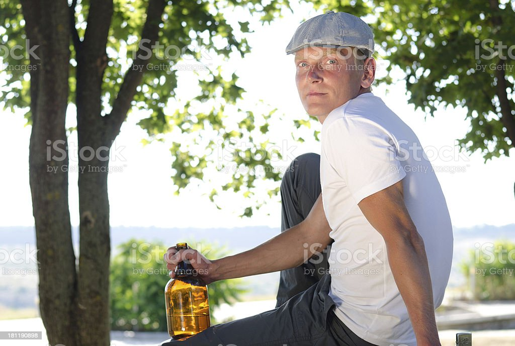 Man sitting relaxing with a bottle of alcohol stock photo