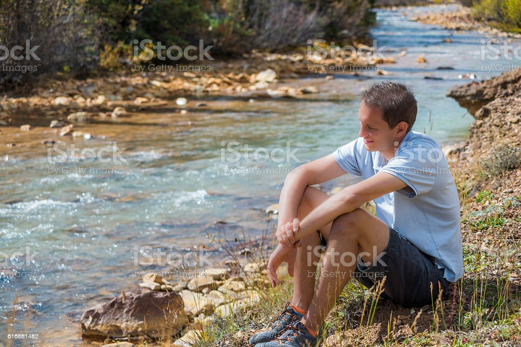 Man sitting smiling by peaceful Mineral Creek in Colorado stock photo