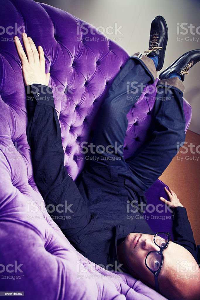 Man sitting strangely in a couch and looking at camera. stock photo