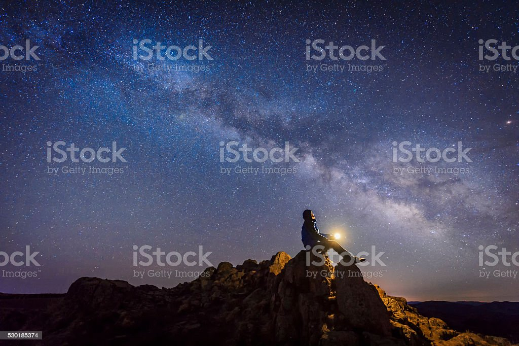 Man sitting under The Milky Way Galaxy stock photo