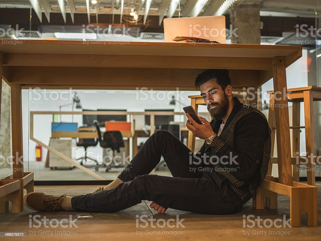 Man sitting under the table and using mobile phone. stock photo