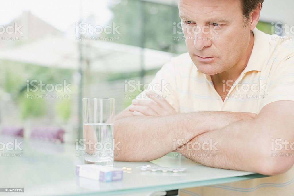 Man sitting with glass of water and box of pills royalty-free stock photo