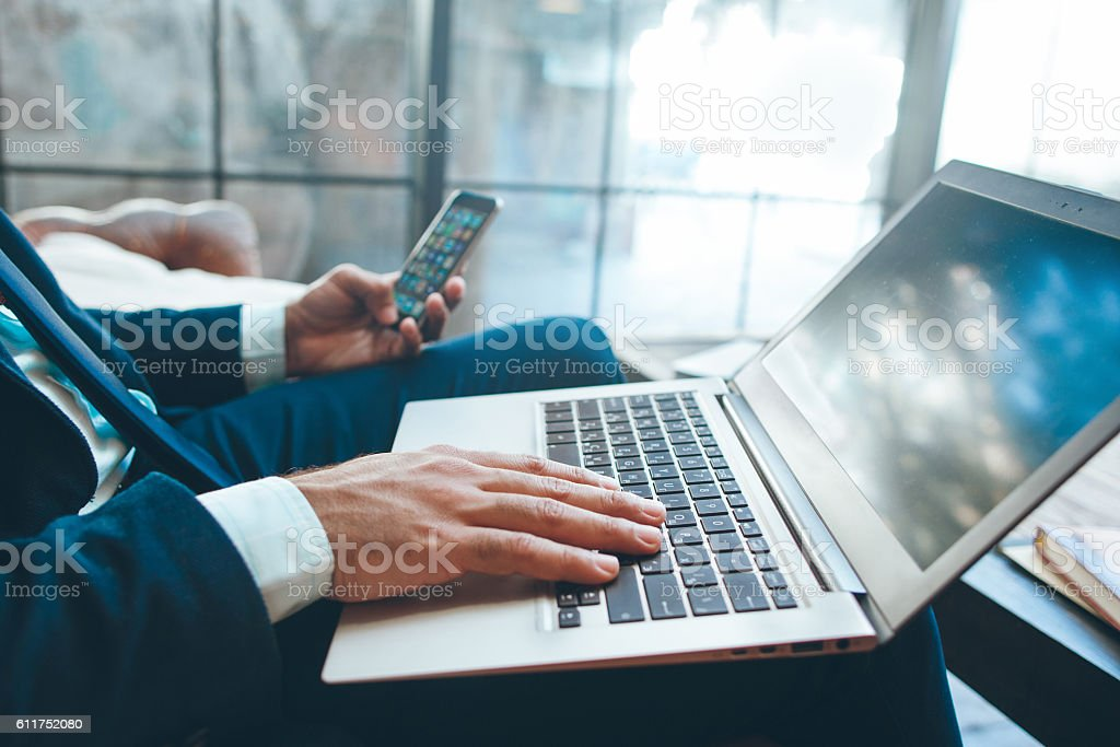 Man sitting with laptop and smartphone stock photo