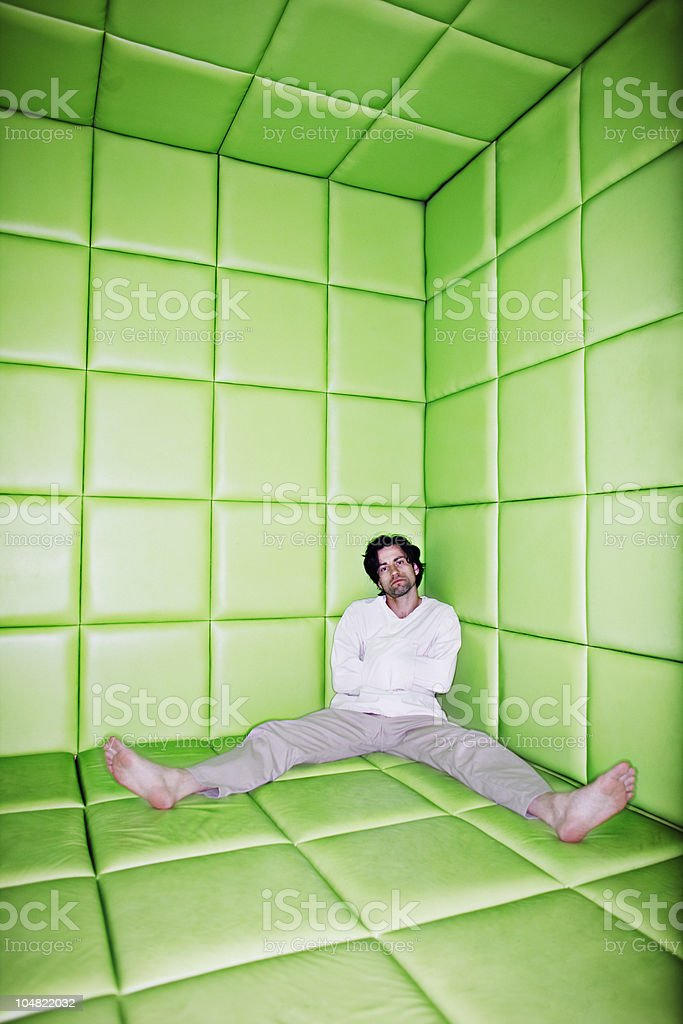 Man sitting with legs apart in padded room royalty-free stock photo